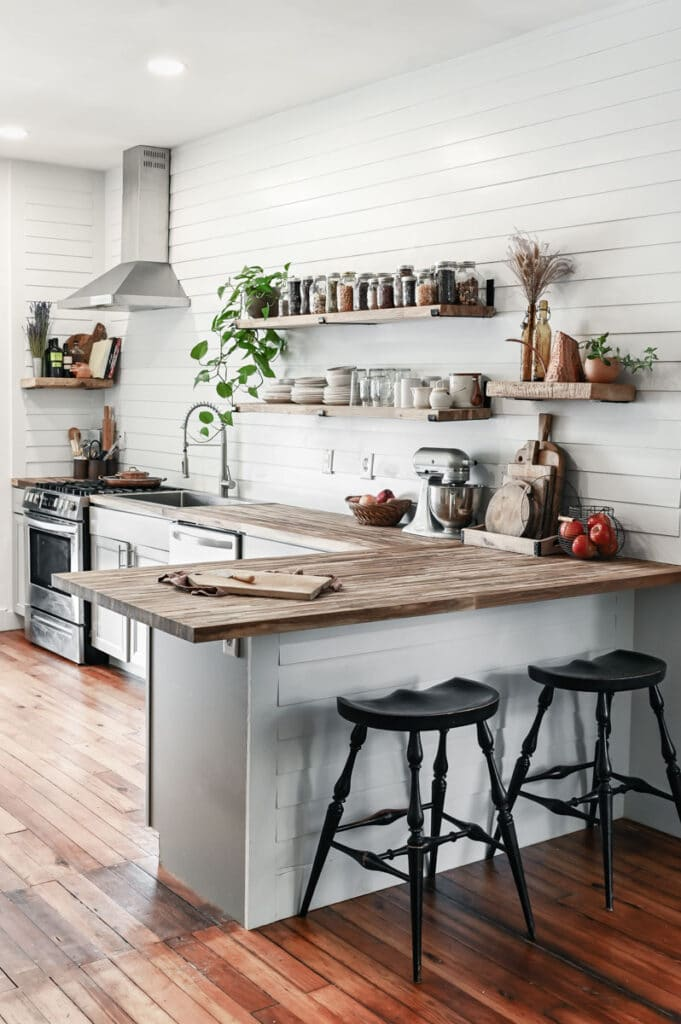 Side view of white kitchen with butcher block counters and open shelves covered in spice jars.