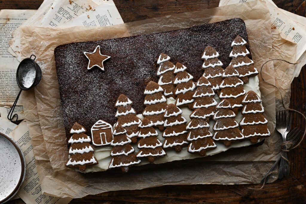 Gingerbread sheet cake topped with Christmas tree shaped cookies on wood table.