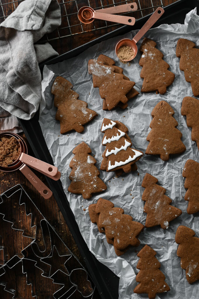 Gingerbread cookies on a cookie tray next to measuring cups.