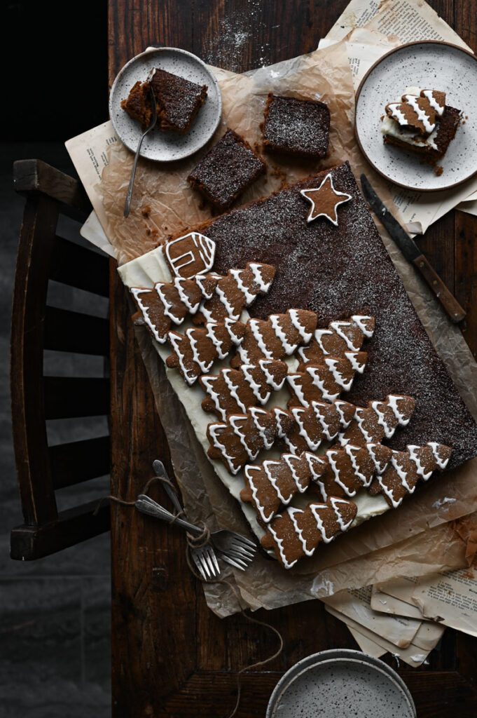 Chocolate cake covered in tree shaped gingerbread cookies.