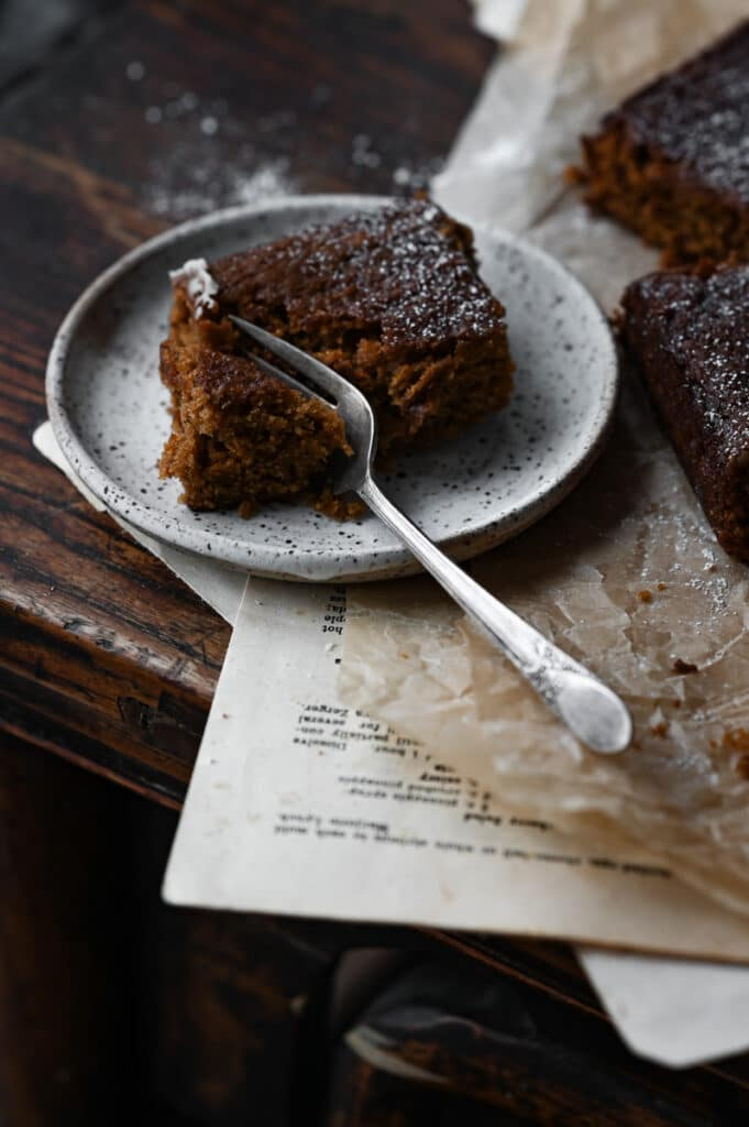 Slice of square cake on plate with a fork.