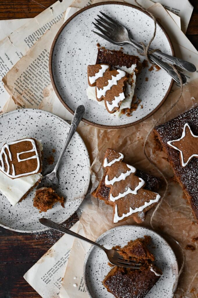 Three plates with a slice of cake and a gingerbread cookie.