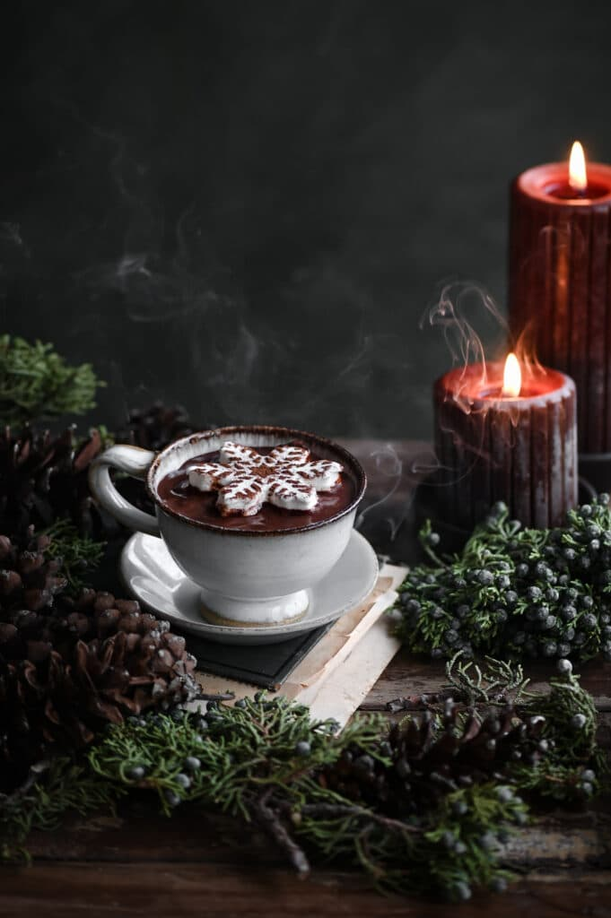 Cup of hot chocolate on a book topped with marshsmallow next to candles.