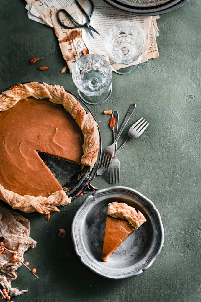 Sweet potato pie with slice missing next to a plated slice on a green table.