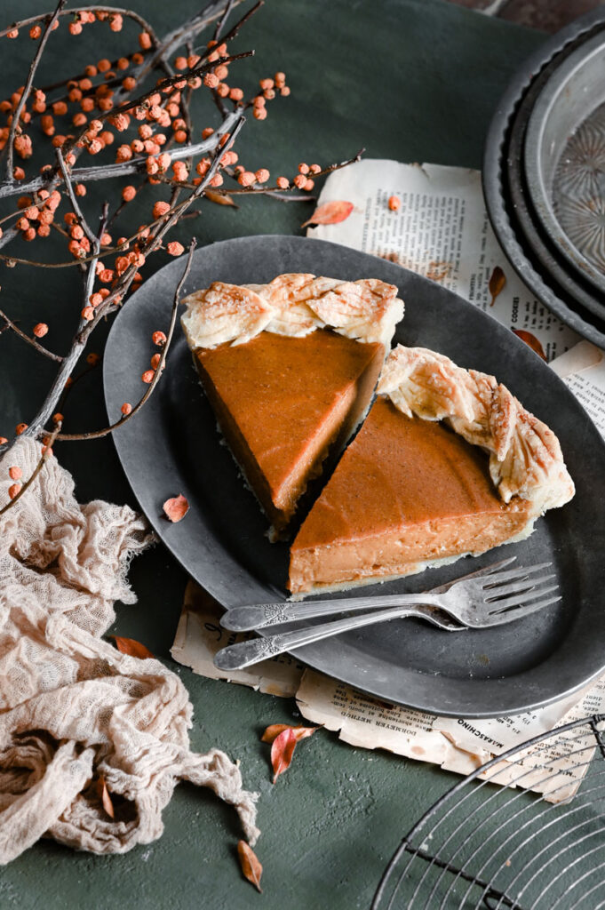 Two slices of sweet potato pie on grey oval dish with forks.