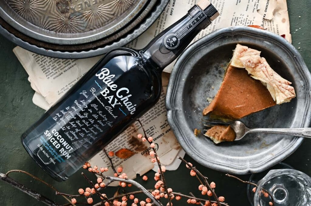 Bottle of spice rum on table next to a slice of pie in a pewter dish.