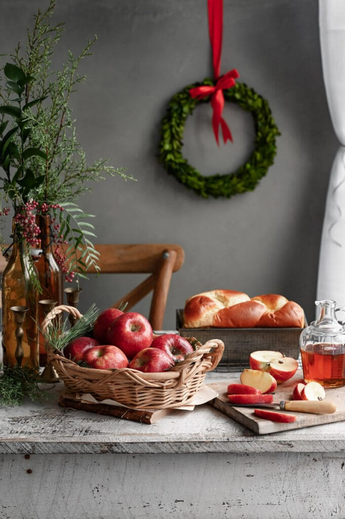 White table with a basket of apples, loaf of bread, jar of syrup and Christmas greenery.