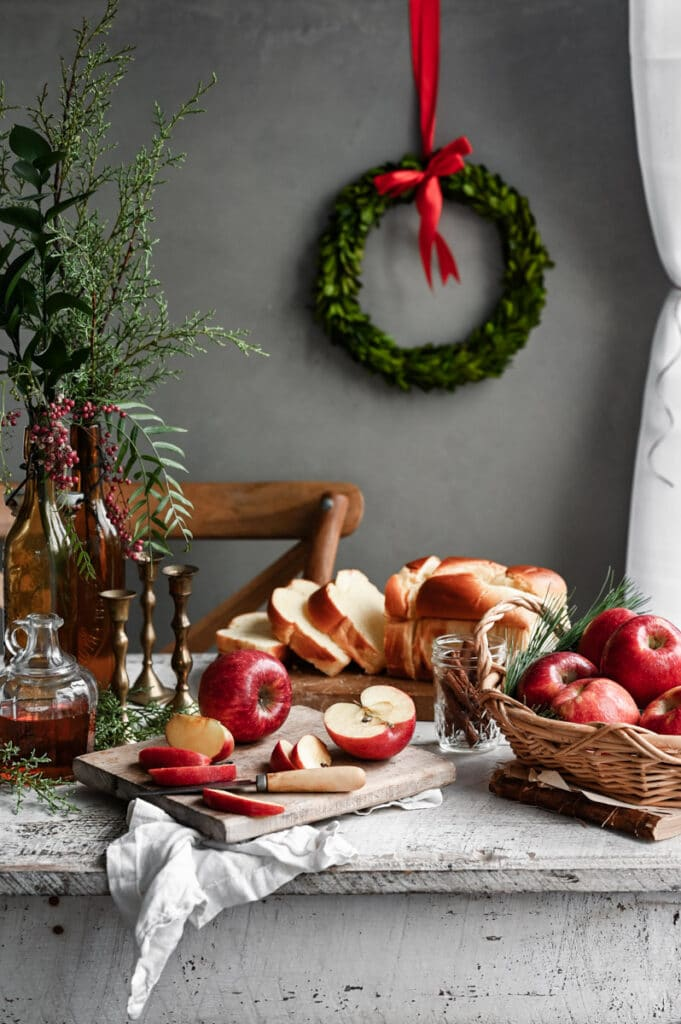 Christmas breakfast table with sliced bread, red apples, syrup, candlesticks, and greenery.