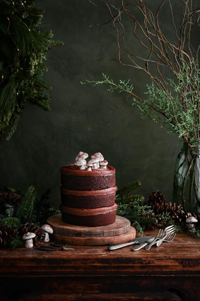 Chocolate layer cake on round wood boards topped with meringue mushrooms.