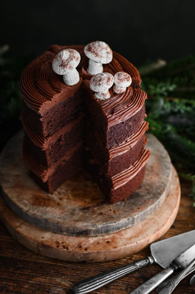 Close up of a chocolate layer cake on wood board with a slice missing.