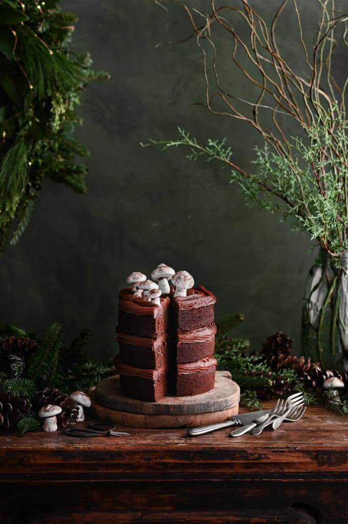 Table scene of a chocolate layer cake on wood boards next to holiday greenery.