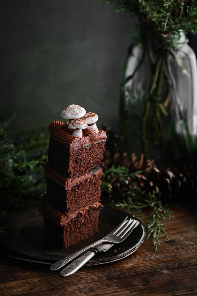 Slice of a three layer chocolate cake topped with meringue mushrooms on a plate.