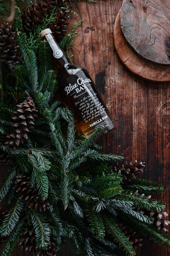 Bottle of vanilla rum on wood table next to holiday greenery.