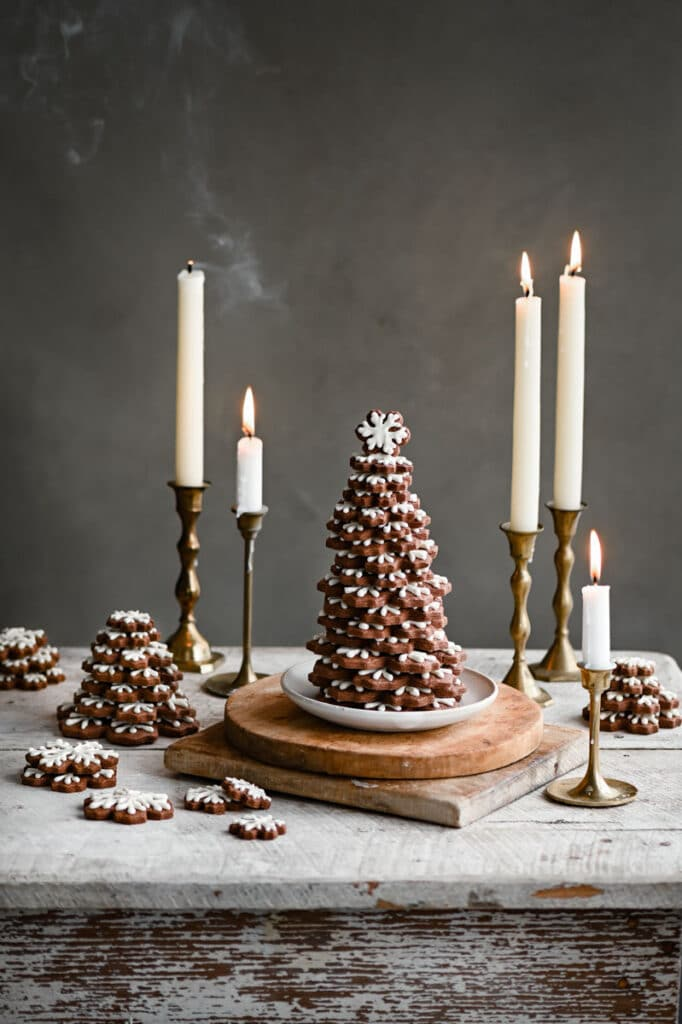 Cookie tree on white table next to white candles.