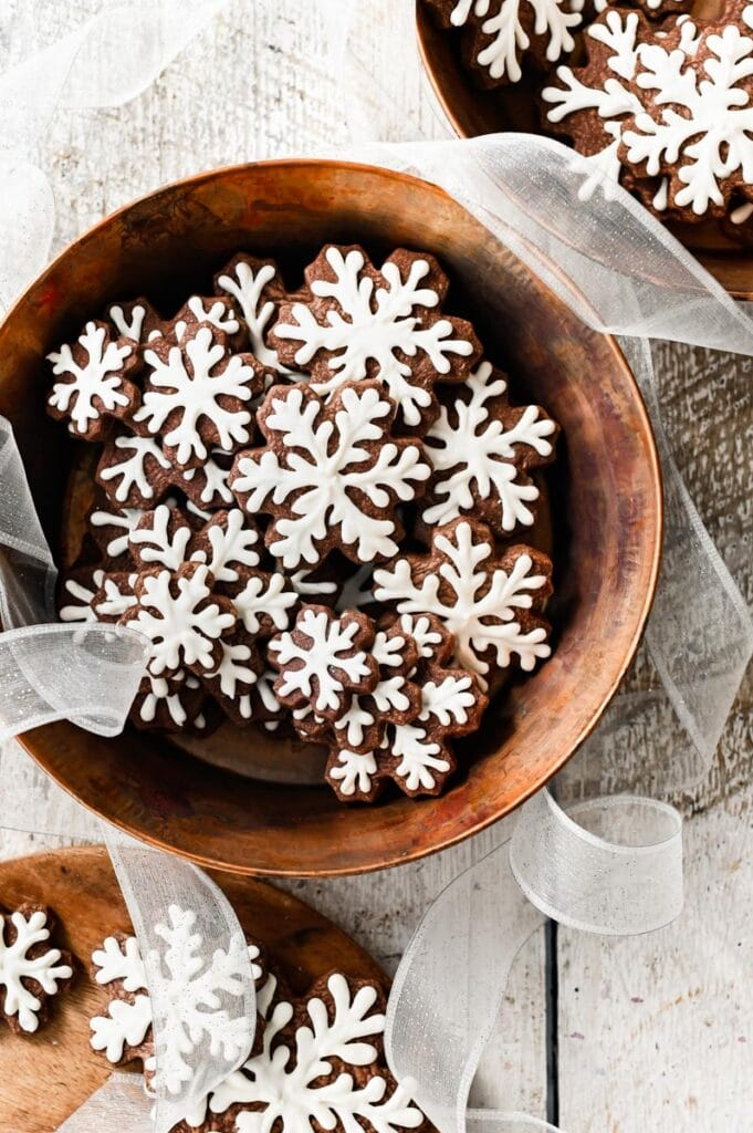 Snowflake frosted cookies in a copper bowl.