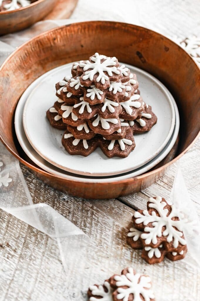 Chocolate snowflake cookies stacked on top of one another in a copper bowl.