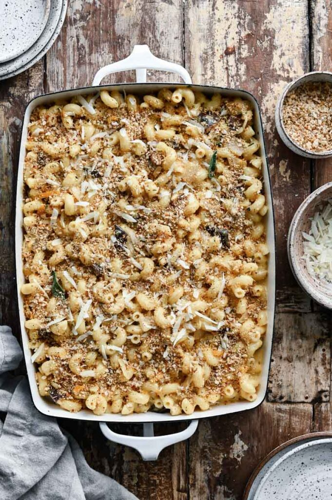 Large casserole dish filled with unbaked mac and cheese on wood table.