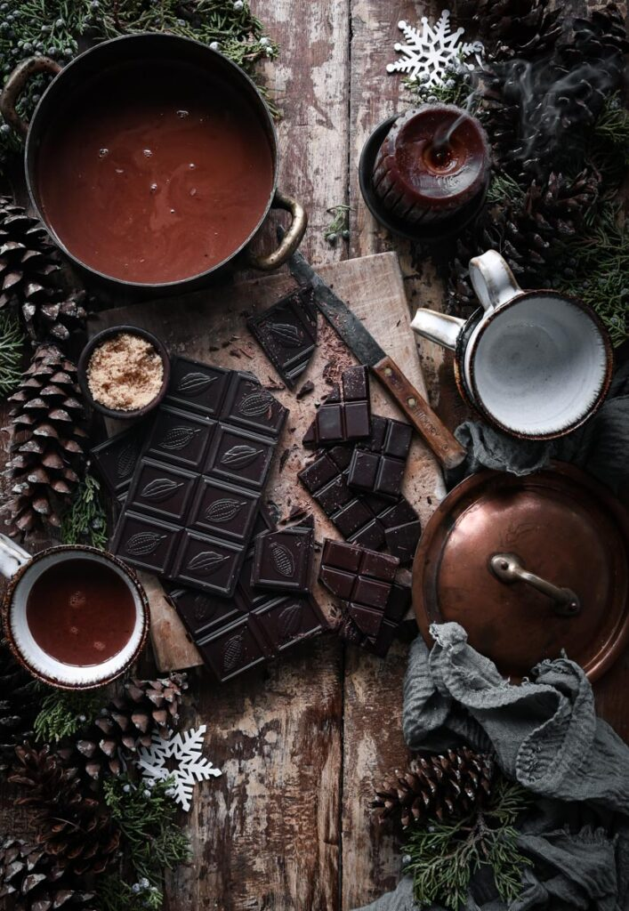 Chopped dark chocolate on cutting board next to pot of hot chocolate on table.