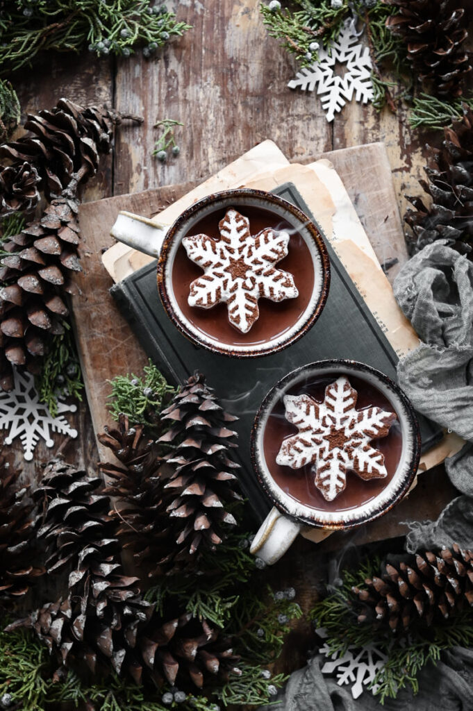 Two mugs of hot chocolate topped with snowflake marshmallow on a wood table surrounded by pinecones.