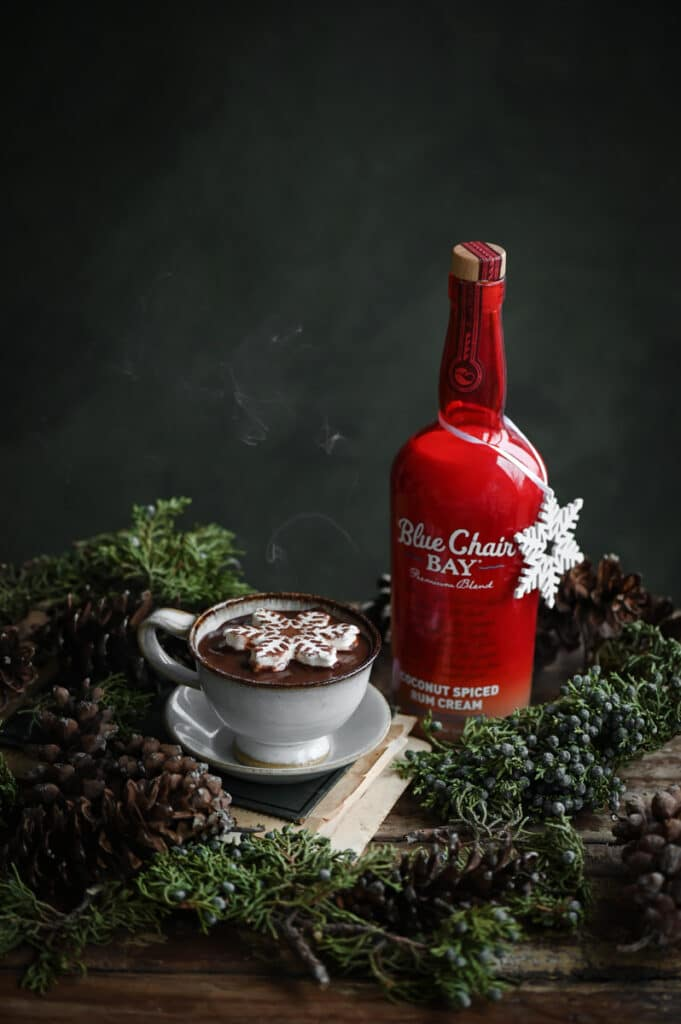 Bottle of rum cream next to cup of hot chocolate on table with holiday greenery.