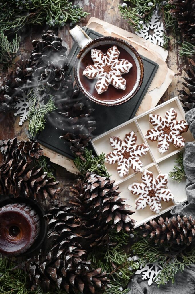 Cup of hot chocolate on table next to tray of snowflake marshmallows and  holiday greenery.