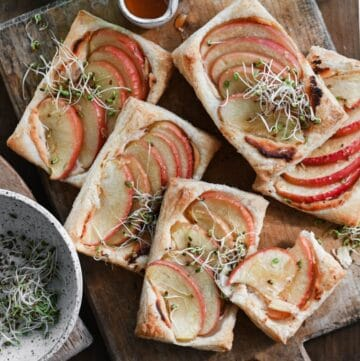 Apple tarts made with puff pastry topped with microgreens on a wooden cutting board.