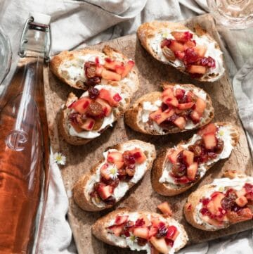 Bruschetta topped with mascarpone cheese and apple chutney on a wood serving board.