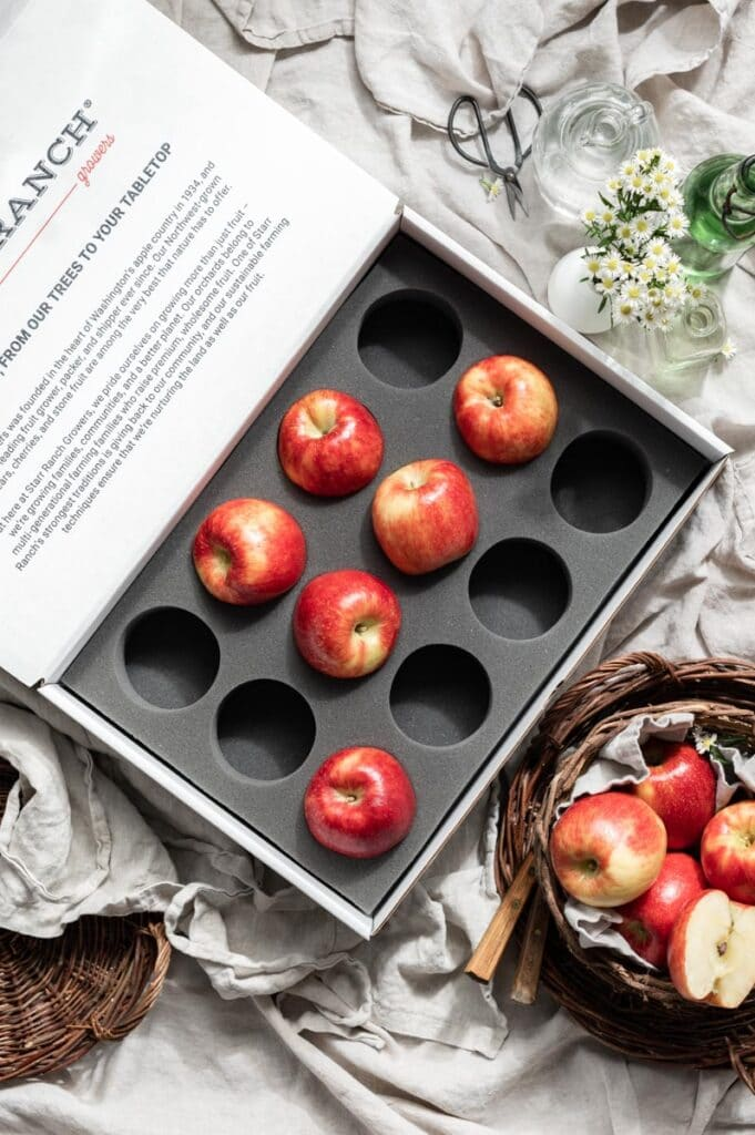 Open large box containing red apples on a linen cloth next to a basket of red apples.