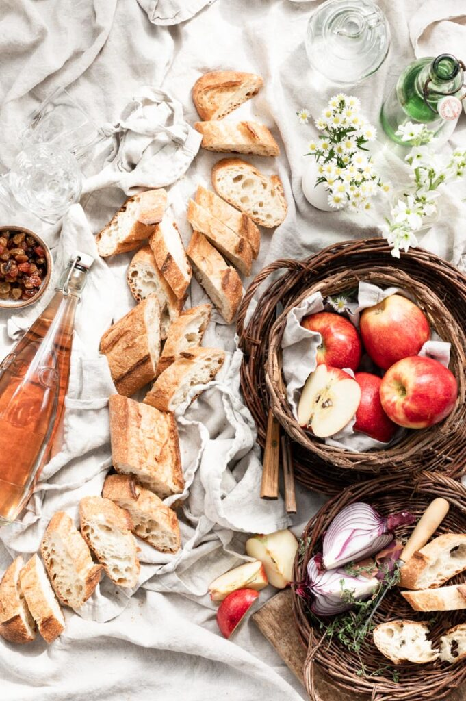 Linen cloth covered in sliced baguettes, a bottle of wine, and a basket of apples.