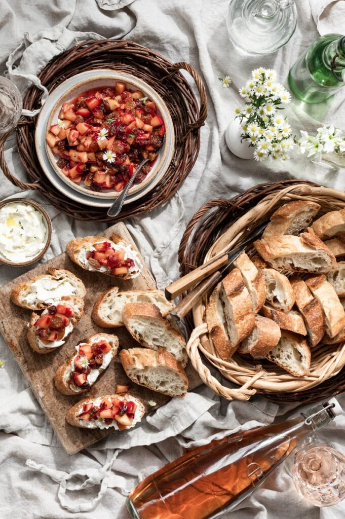 Table scene with apple bruschetta on a cutting board, bowl of apple chutney, and basket of bread.
