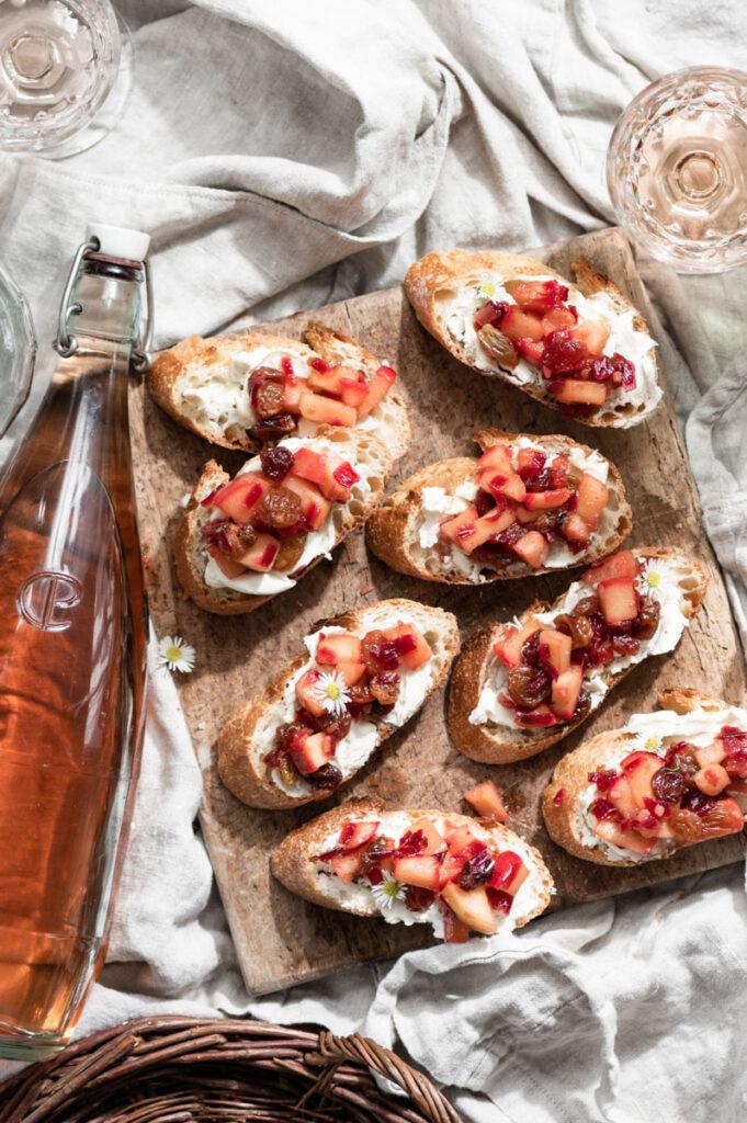 Apple bruschetta on a wood board next to a bottle of rose wine.