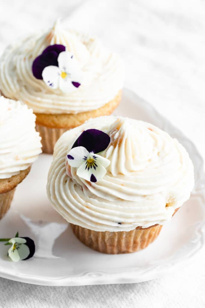 Closeup of an white frosted cupcake topped with flowers.