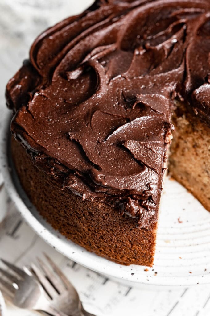 Closeup of a yellow cake with chocolate frosting and a slice missing. and