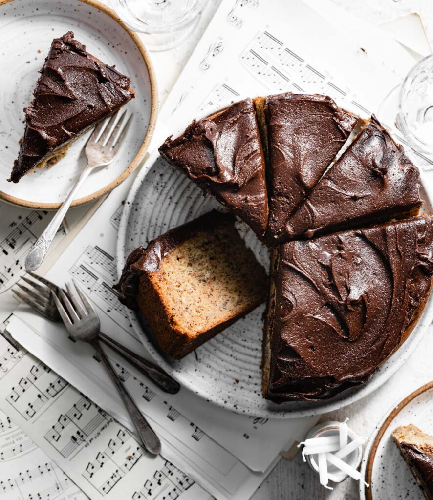 Chocolate frosted cake with cut slices on top of music sheets.