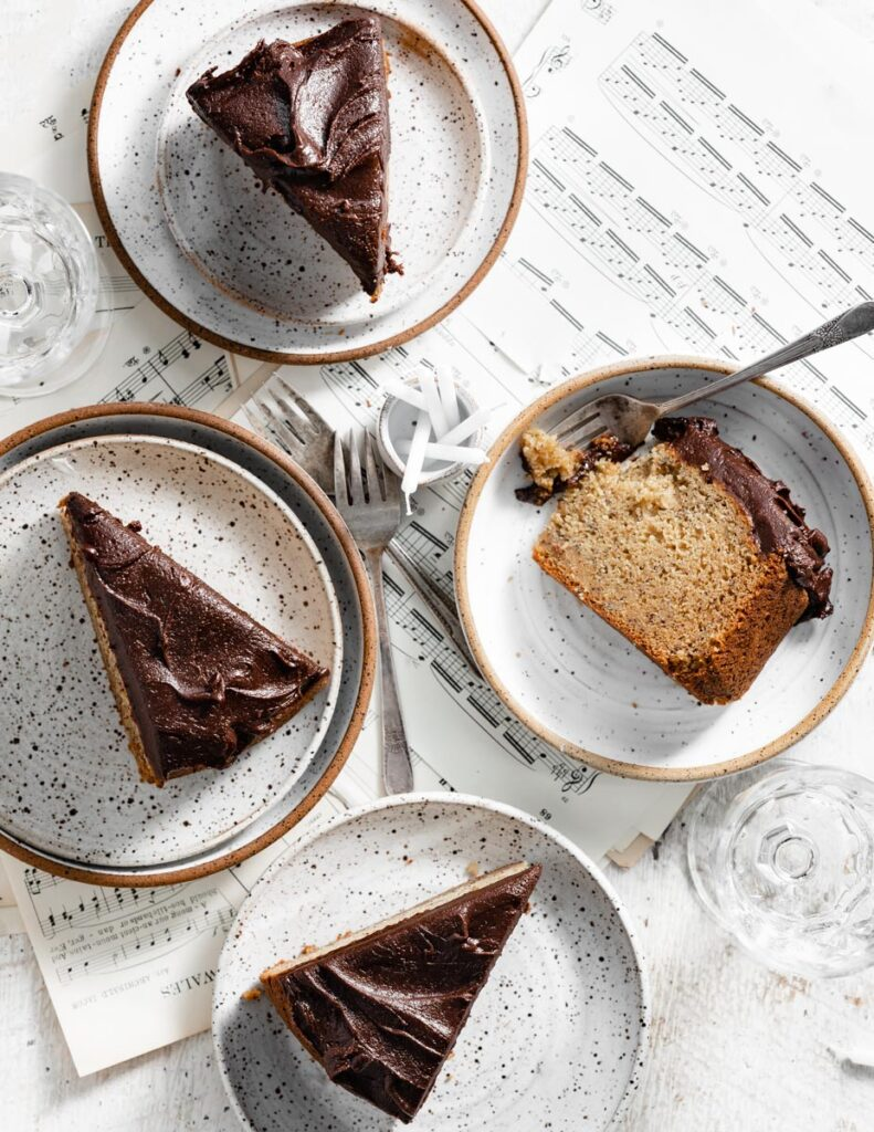 Four slices of yellow cake with chocolate frosting on white speckled plates.