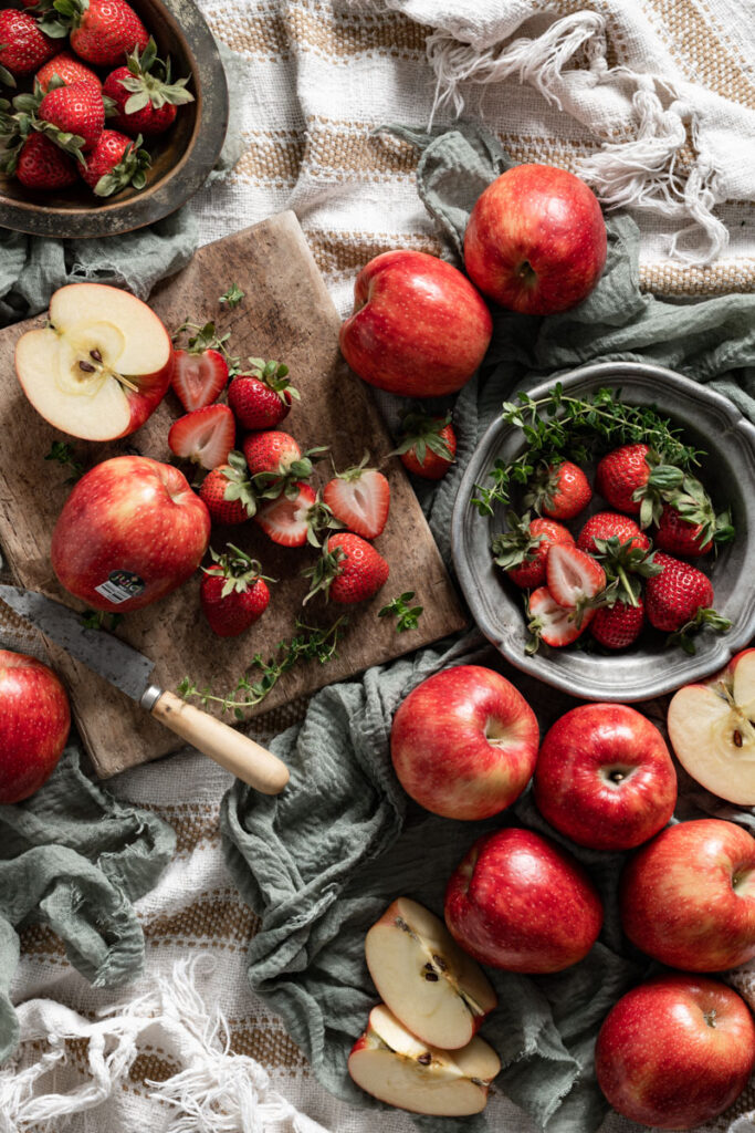 Fresh apples and sliced strawberries on a cutting board.