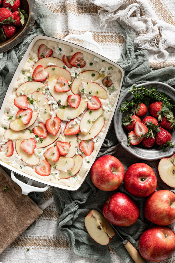 Focaccia dough in a pan topped with strawberries and sliced apples.