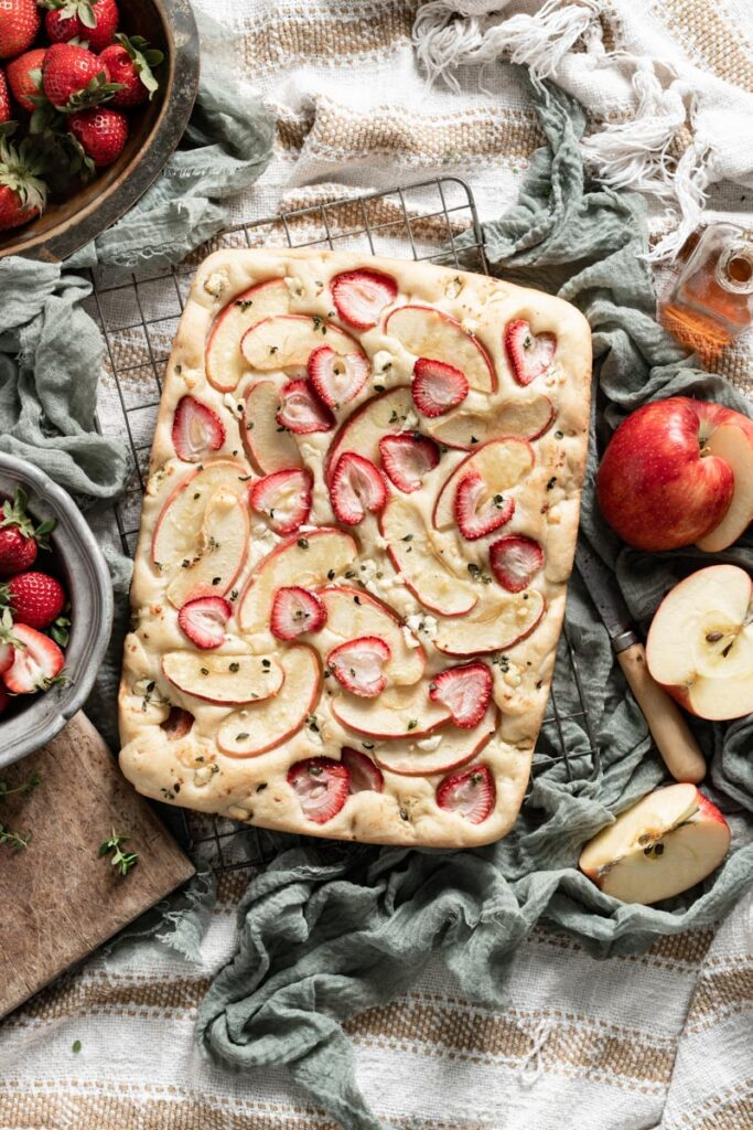 Fruit topped focaccia bread on table next to apples and sliced strawberries.