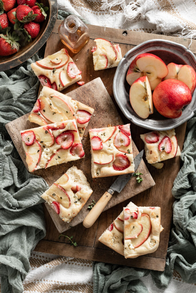 Sliced fruit focaccia bread on cutting board next to bowl of apples.
