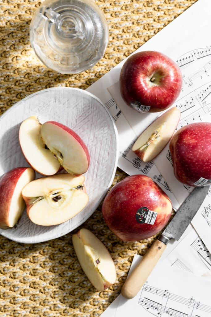 Red apples on a white plate and music sheets set on a blanket.
