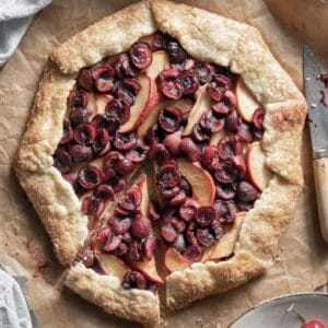 Closeup of a cherry and peach galette with a slice cut.