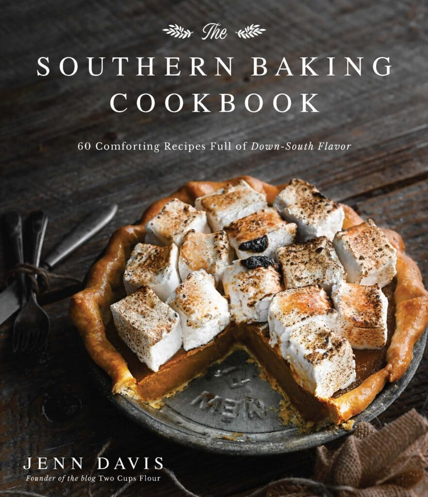 Cookbook cover with a marshmallow topped pumpkin pie on table missing a slice.