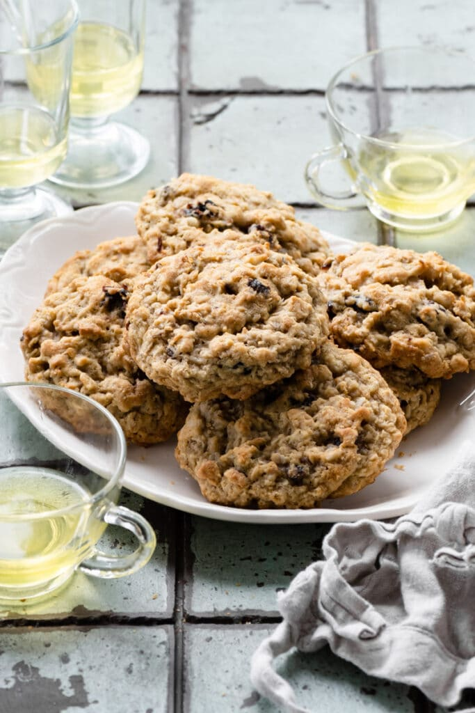 Oatmeal cookies stacked on a white plate.