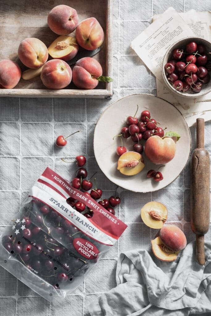 Bag of dark red cherries pouring out onto a table with sliced peaches.
