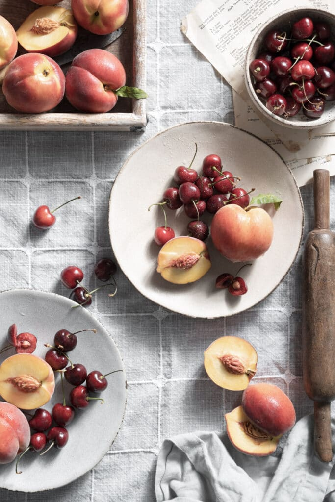 Fresh cherries and sliced yellow peaches in plates on linen covered table.