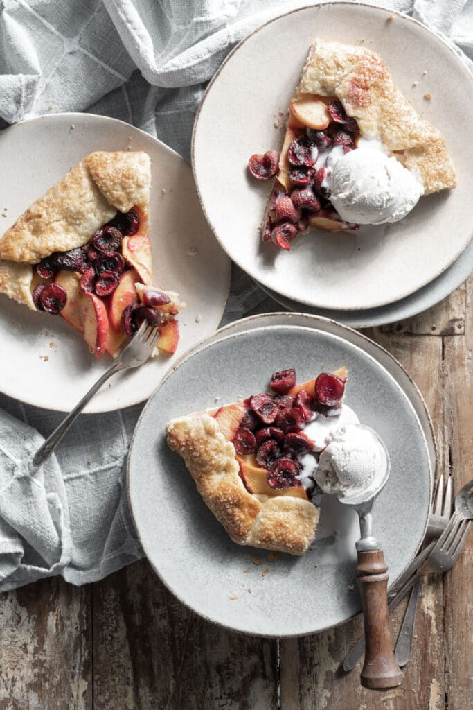 Three slices of fruit pie on plates topped with vanilla ice cream.