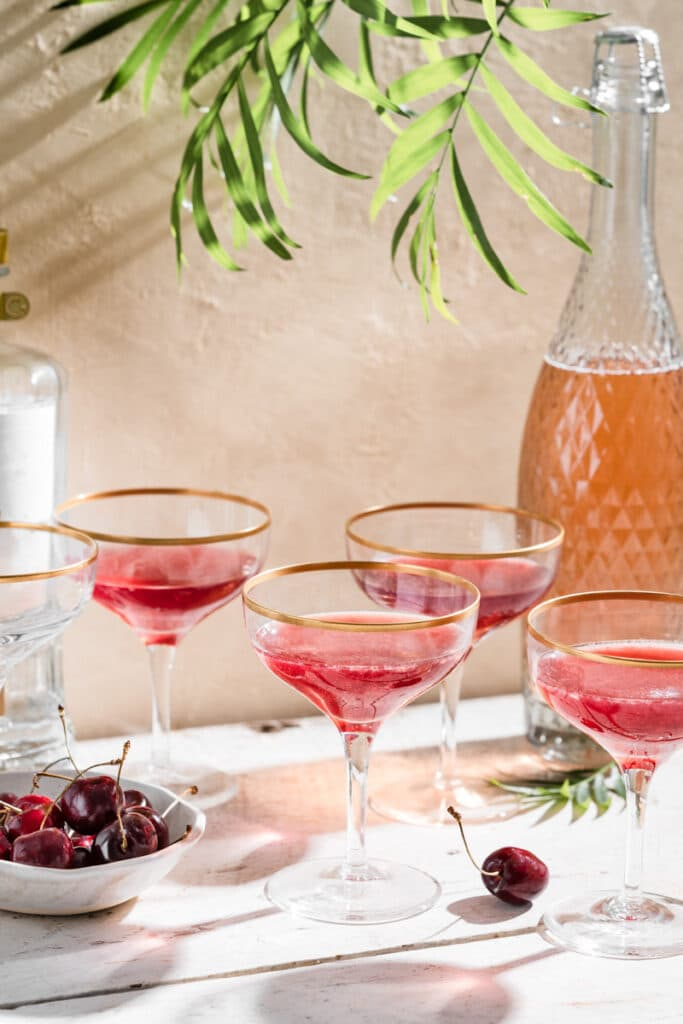 Four stemmed wine glasses filled with cherry cocktail on table next to bowl of cherries.