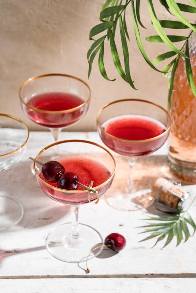 Three cherry cocktails in stem glasses garnished with fresh cherries.