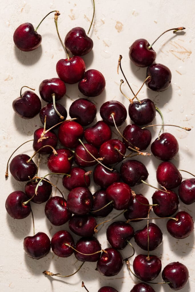 Sweet dark cherries with stems spread out on peach table.