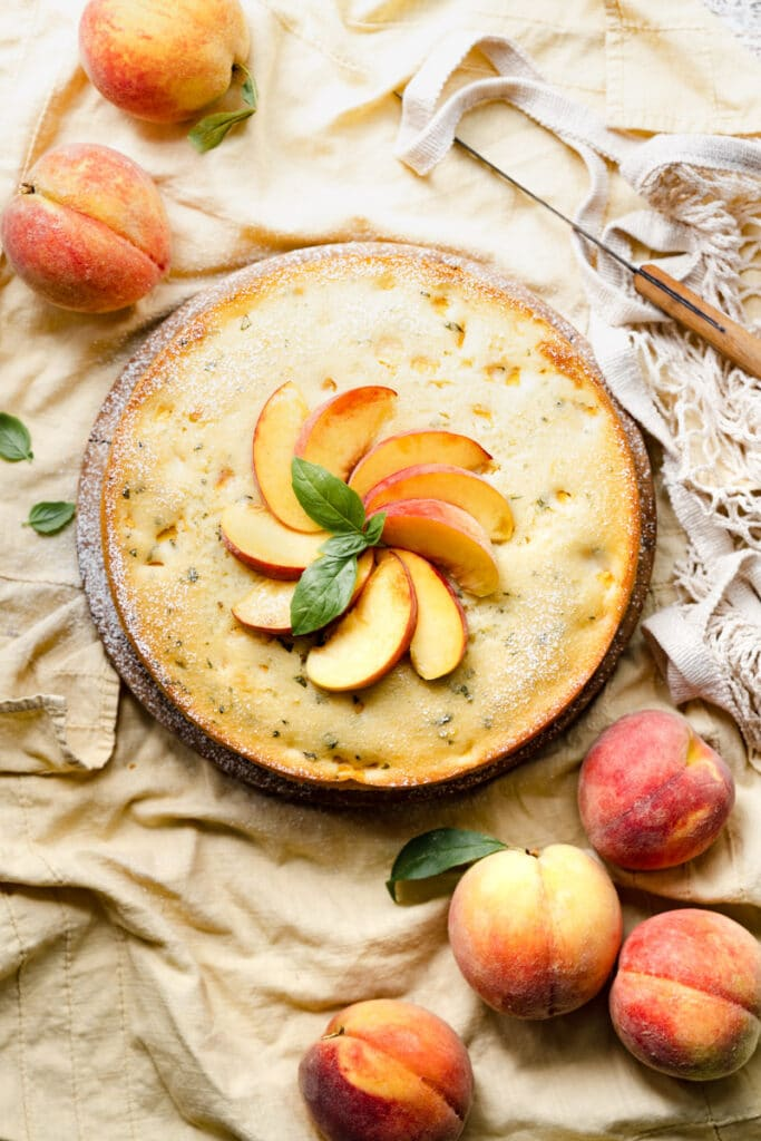 Single layer cake topped with yellow peaches and basil on a wood board.